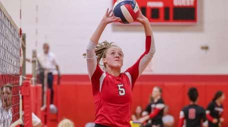 Caitlin Dellecave of Patchogue-Medford sets the ball during