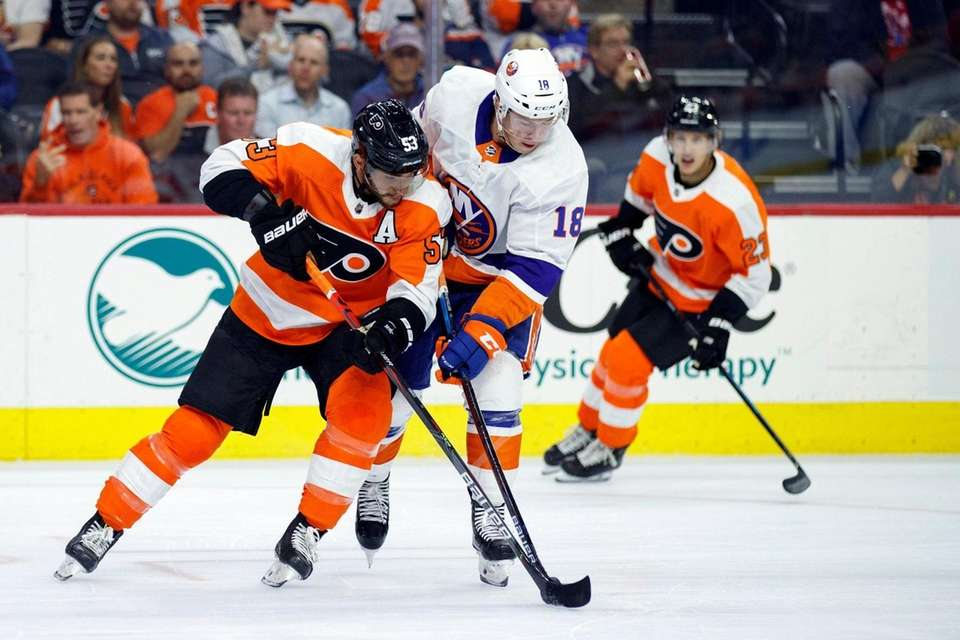 The Flyers' Shayne Gostisbehere, left, and the Islanders'