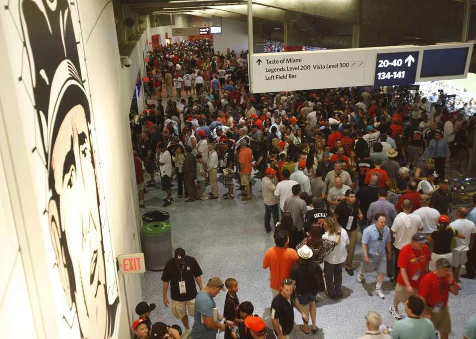 Baseball fans mill about an upper concourse before
