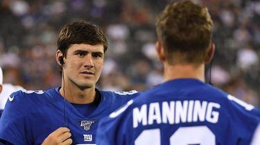 Giants quarterback Daniel Jones talks to quarterback Eli