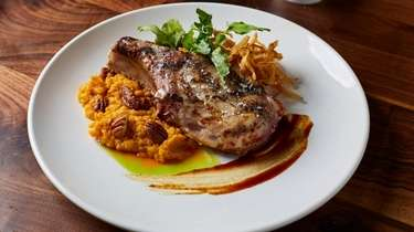 Grilled, center-cut pork chop arrives atop a sweet-potato