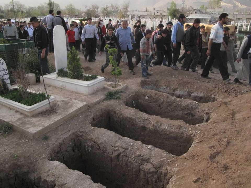 Mourners walk past open graves at a cemetery