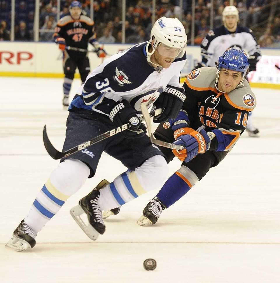Micheal Haley battles for the puck with Winnipeg