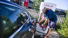 Jeff Wheeler, of Amityville, plugs in his Tesla