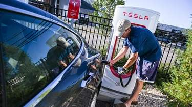 Jeff Wheeler, of Amityville, plugs in his Tesla