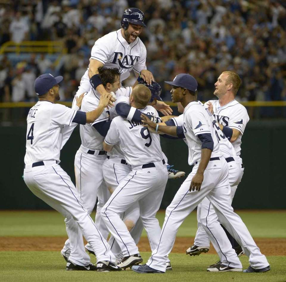 Tampa Bay Rays' Carlos Pena is swarmed by