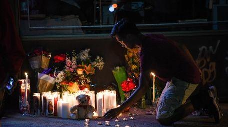 Gabriel DeGuzman, 15, of Oceanside lights a candle
