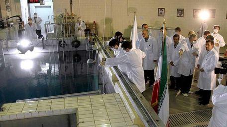 Iranian President Mahmoud Ahmadinejad, right, is escorted by