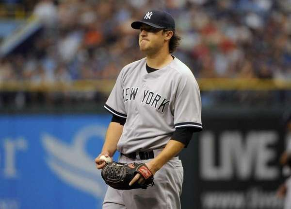 Yankees starting pitcher Phil Hughes reacts after walking