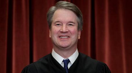 Associate Justice Brett Kavanaugh sits with fellow Supreme