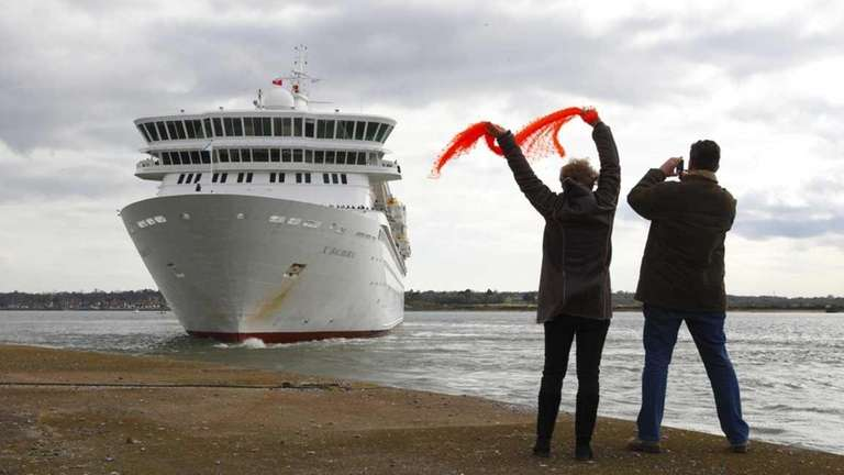 People wave at the MS Balmoral cruise ship