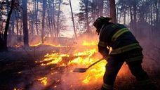 A firefighter battles a blaze in Manorville off