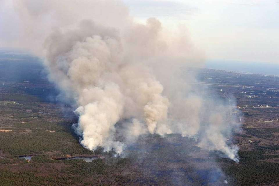 Plumes of smoke rise from the massive brush