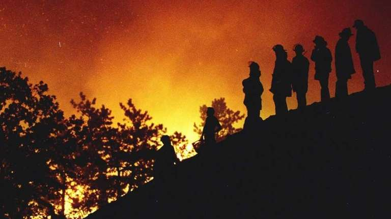 Firefighters stand on a mound as the Sunrise
