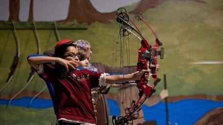 Omar Anees, 9, watches as his arrow flies