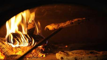 Pizzas bake in the wood burning oven at