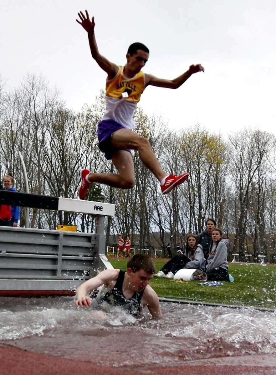A Sayville runner jumps over a fallen Bayport