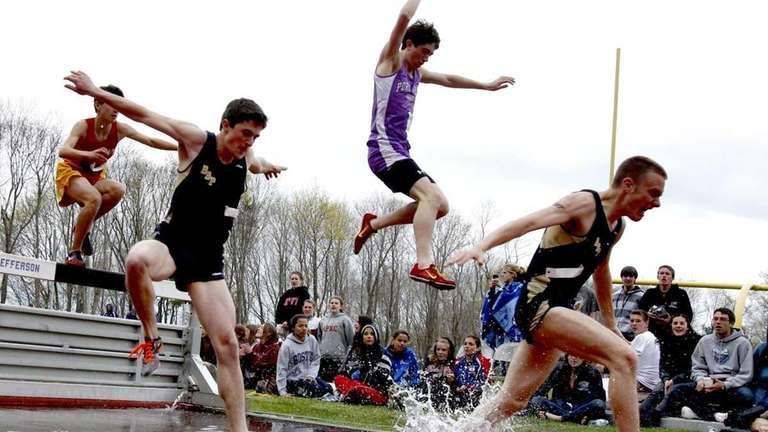 Runners in the boys open 2,000m steeplechase clear