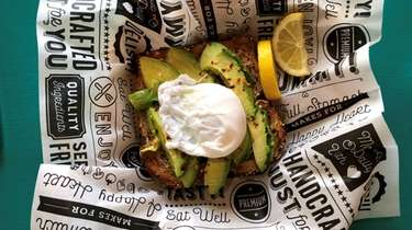 Avocado toast topped by a poached egg at