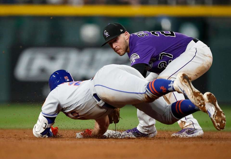 Colorado Rockies shortstop Trevor Story, back, tags out