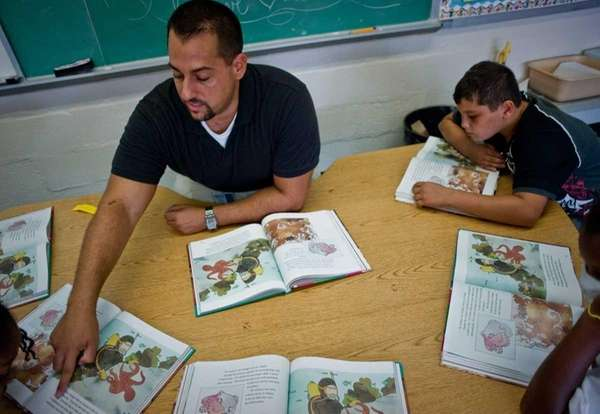 Teacher Steven Ferretti helps students in his class