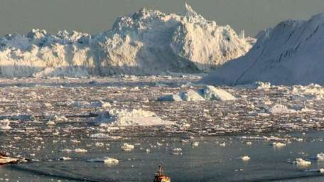 A boat skims through the melting ice in