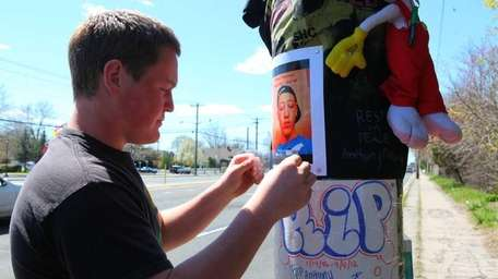 Matthew Namdar hangs a photo of Anthony D'Alessandro,
