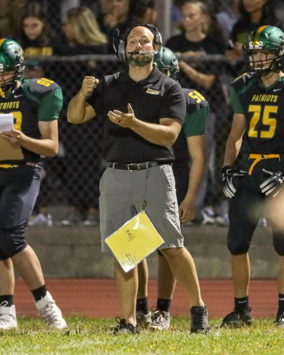 Ward Melville's head coach Chris Boltrek signals to