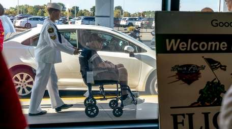 A veteran, accompanied by a naval cadet, arrives