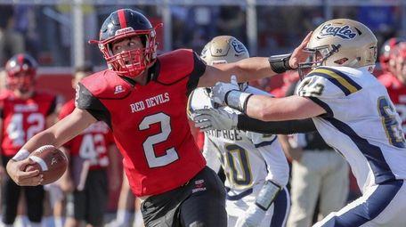 Plainedge quarterback Dan Villari fends off a Bethpage