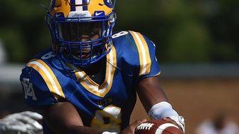 Jaheim Perry #8, East Meadow quarterback, sells a