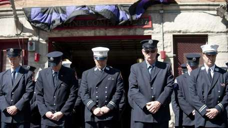 Members of FDNY Engine 237 bow their heads