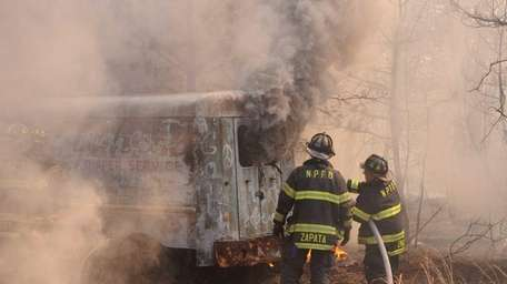 A vehicle burns in the backyard of a