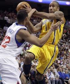 Philadelphia 76ers' Evan Turner, left, fouls Indiana Pacers'