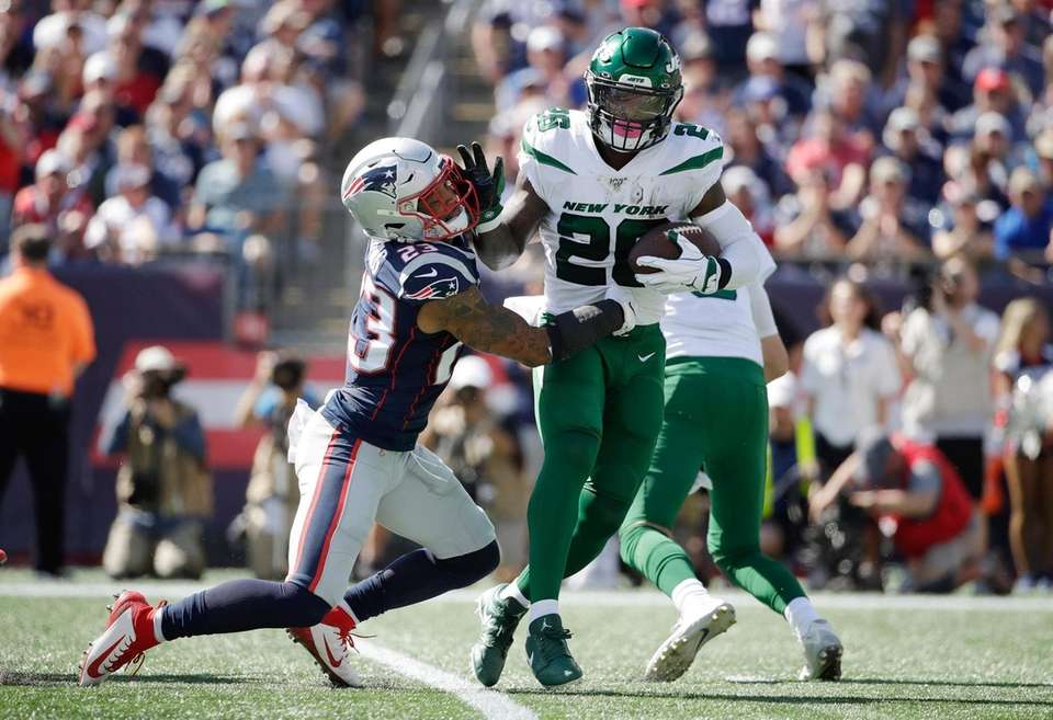 Jets running back Le'Veon Bell, right, tries to