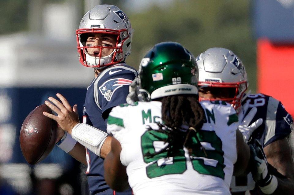 Patriots quarterback Jarrett Stidham, left, looks for a