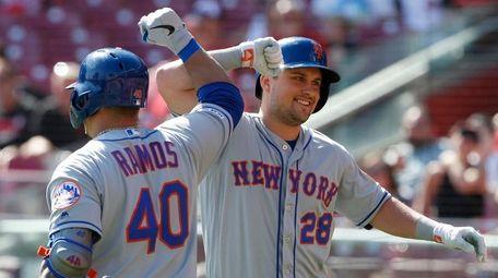 The Mets' J.D. Davis bumps elbows with Wilson