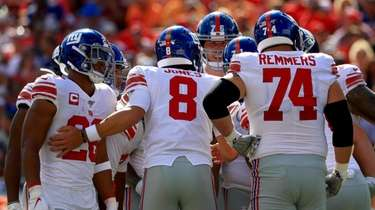 Giants quarterback Daniel Jones huddles with teammates against