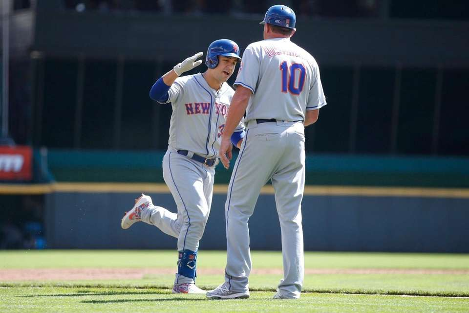 The Mets' Michael Conforto is congratulated by third