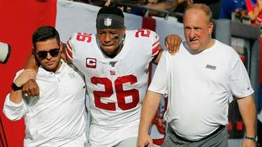 Giants running back Saquon Barkley gets helped off