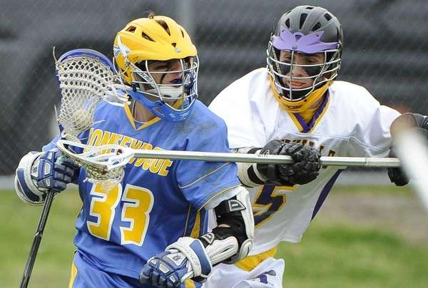 Comsewogue attacker Justin Carlson is pressured by Sayville's