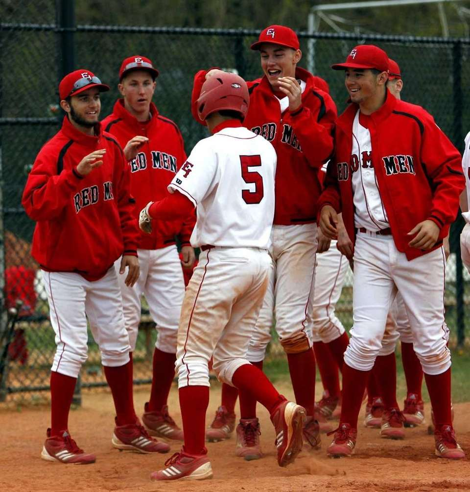 East Islip teammates congratulate Nick Osburn (5) at