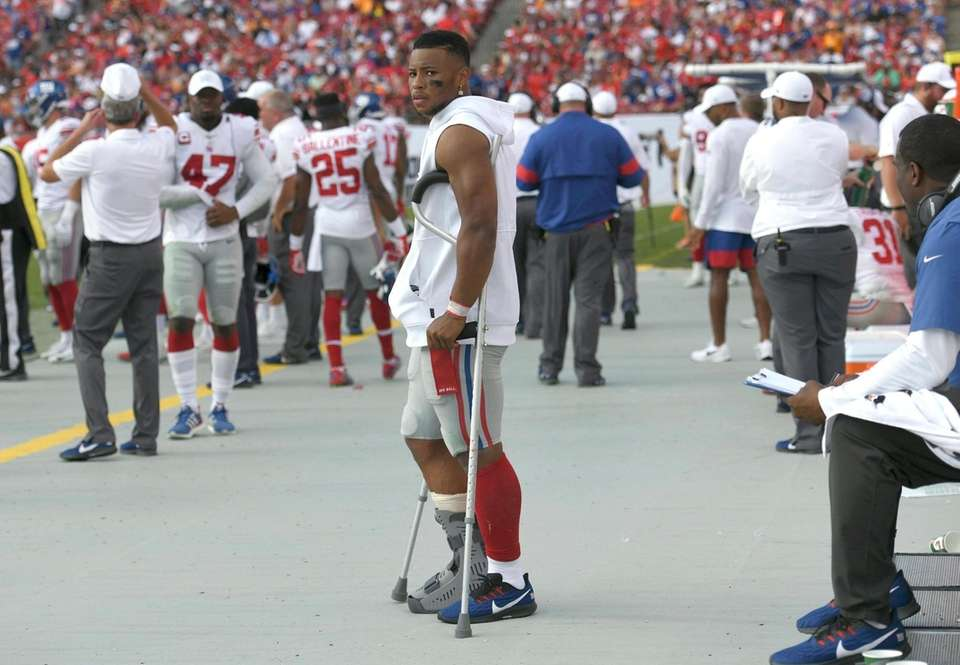 Giants running back Saquon Barkley stands on crutches