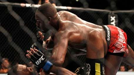 Jon Jones, right, punches as he jumps on