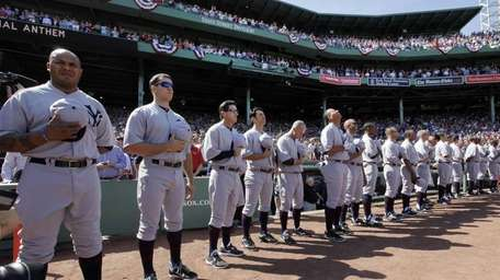 New York Yankees players stand for the national