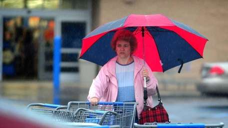 Denise Holady of Northport uses an umbrella to