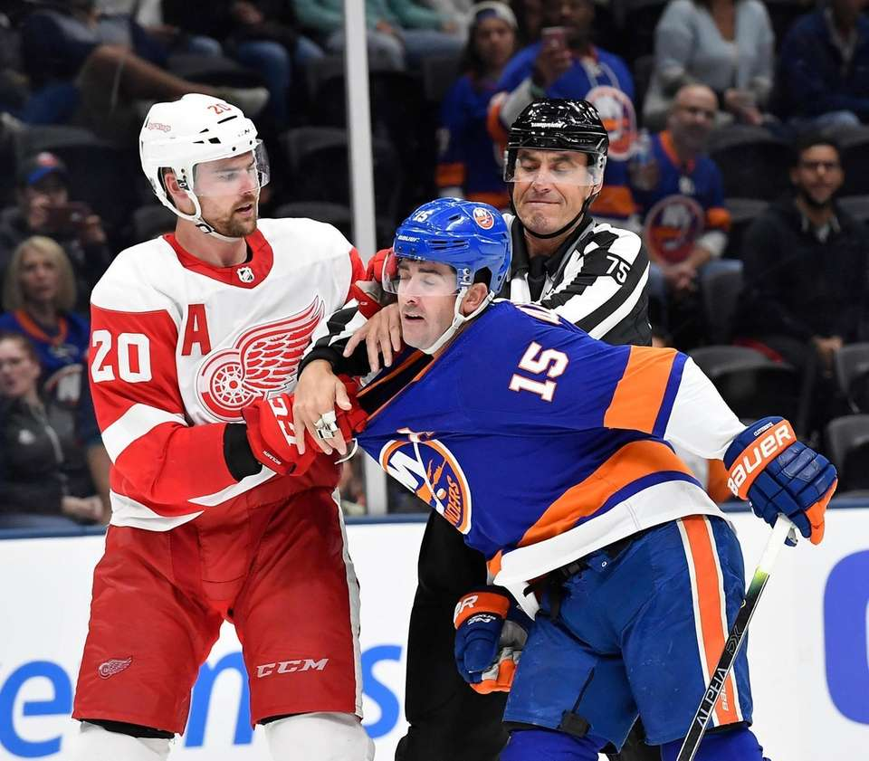Linesman Derek Amell seperates Dylan McIlrath of the