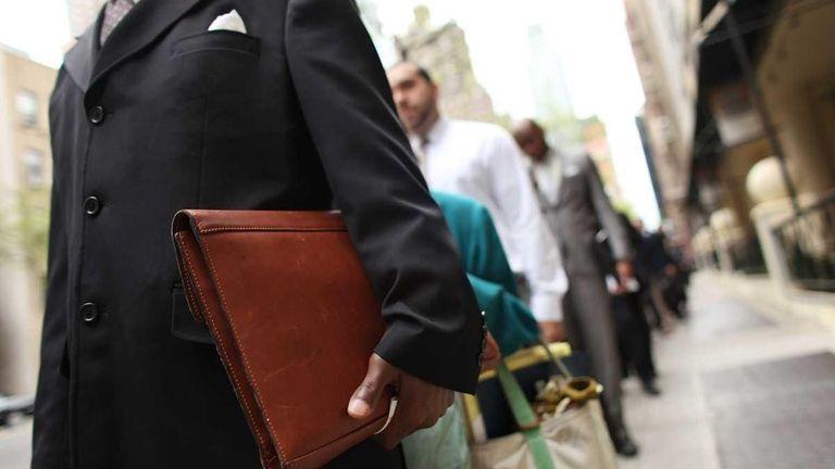 Job seekers line-up to attend a job fair