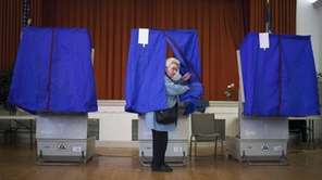 Lilyan Maitan stands in a voting booth during