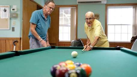 Fred Gomez, 104, right, takes aim at the
